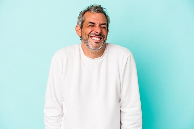 Blanke man van middelbare leeftijd geïsoleerd op blauwe achtergrond lacht en sluit de ogen, voelt zich ontspannen en gelukkig.