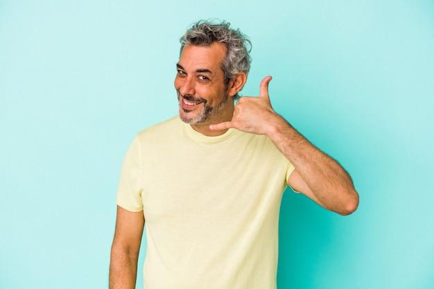 Blanke man van middelbare leeftijd geïsoleerd op blauwe achtergrond met een mobiel telefoongesprek gebaar met vingers.