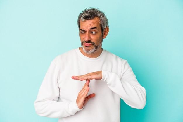 Blanke man van middelbare leeftijd geïsoleerd op blauwe achtergrond met een time-out gebaar.