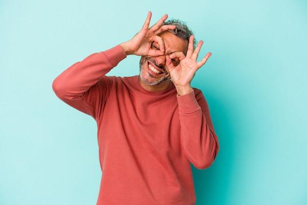 Blanke man van middelbare leeftijd geïsoleerd op blauwe achtergrond met goed teken boven de ogen