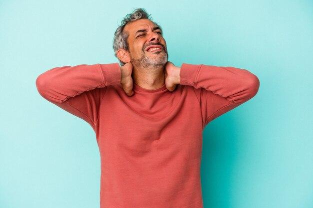Blanke man van middelbare leeftijd geïsoleerd op blauwe achtergrond met nekpijn als gevolg van een zittende levensstijl.