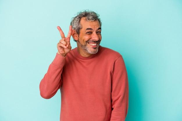Blanke man van middelbare leeftijd geïsoleerd op blauwe achtergrond met nummer twee met vingers.