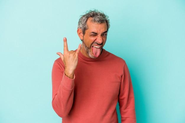 Blanke man van middelbare leeftijd geïsoleerd op blauwe achtergrond met rotsgebaar met vingers