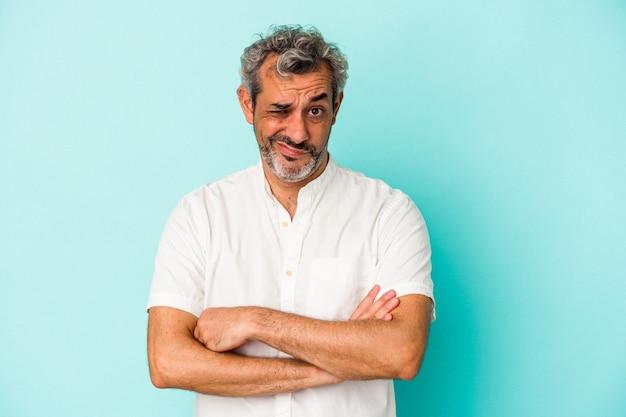 Blanke man van middelbare leeftijd geïsoleerd op blauwe achtergrond ongelukkig in de camera kijken met sarcastische uitdrukking.