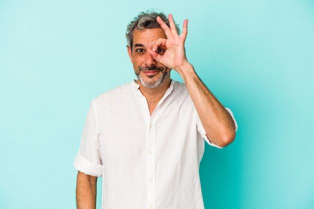 Blanke man van middelbare leeftijd geïsoleerd op blauwe achtergrond opgewonden houden ok gebaar in de gaten.