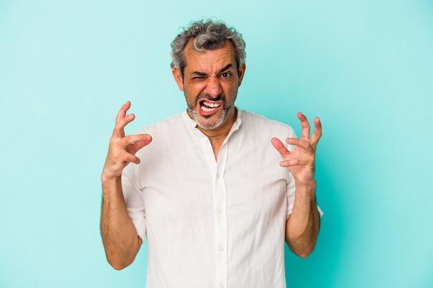 Blanke man van middelbare leeftijd geïsoleerd op blauwe achtergrond schreeuwen van woede.