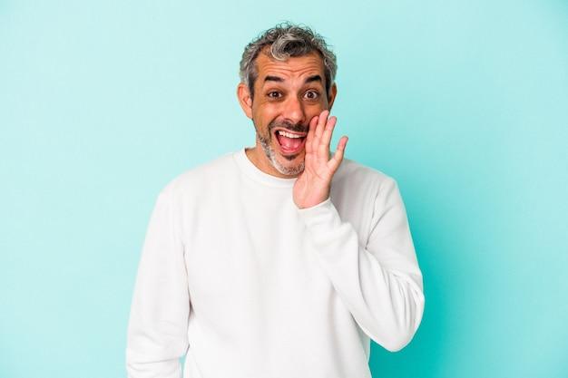 Blanke man van middelbare leeftijd geïsoleerd op blauwe achtergrond schreeuwt luid, houdt ogen open en handen gespannen.