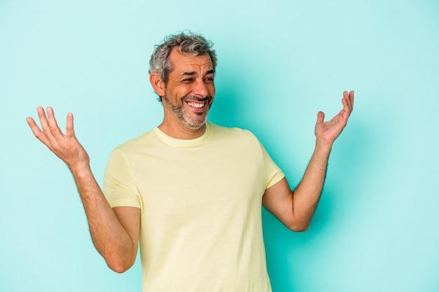 Blanke man van middelbare leeftijd geïsoleerd op blauwe achtergrond vrolijk veel lachen. geluk concept.