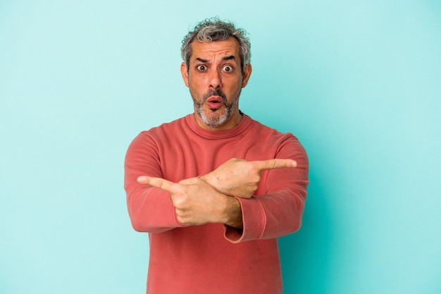 Blanke man van middelbare leeftijd geïsoleerd op blauwe achtergrond wijst zijwaarts, probeert te kiezen tussen twee opties.