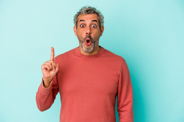 Blanke man van middelbare leeftijd geïsoleerd op blauwe achtergrond wijzend ondersteboven met geopende mond.