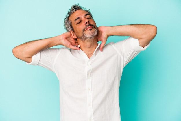 Blanke man van middelbare leeftijd geïsoleerd op blauwe achtergrond zelfverzekerd gevoel, met handen achter het hoofd.