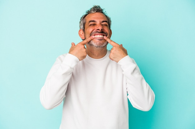 Blanke man van middelbare leeftijd geïsoleerd op een blauwe achtergrond glimlacht, wijzende vingers naar de mond.
