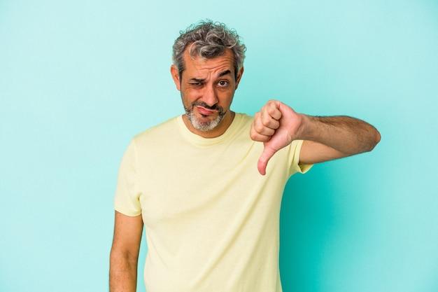 Blanke man van middelbare leeftijd geïsoleerd op een blauwe achtergrond met duim naar beneden en het uiten van afkeer.