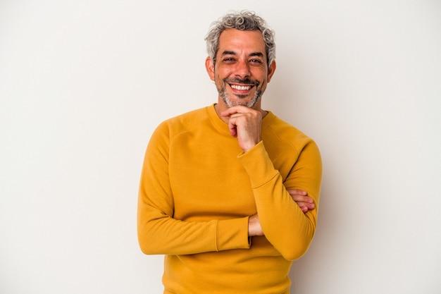 Blanke man van middelbare leeftijd geïsoleerd op een witte achtergrond glimlachend gelukkig en zelfverzekerd, kin met de hand aan te raken.