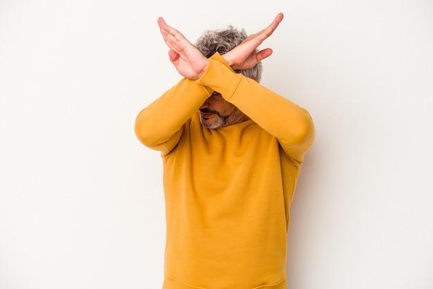 Blanke man van middelbare leeftijd geïsoleerd op een witte achtergrond houden twee armen gekruist, ontkenning concept.