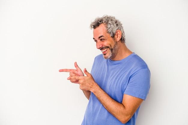 Blanke man van middelbare leeftijd geïsoleerd op een witte achtergrond wijst met duimvinger weg, lachend en zorgeloos.