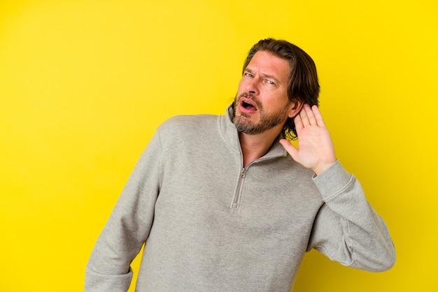 Blanke man van middelbare leeftijd geïsoleerd op gele achtergrond die een roddel probeert te luisteren.