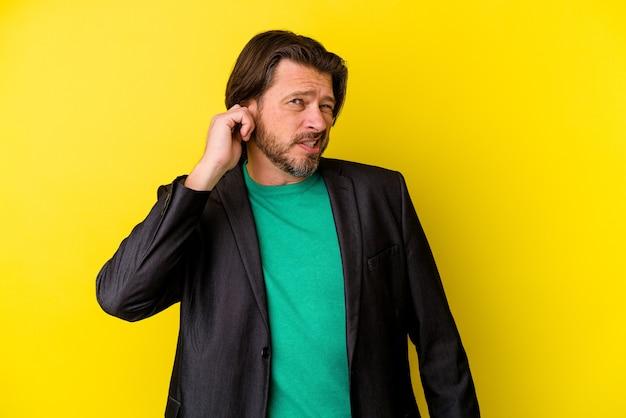 Blanke man van middelbare leeftijd geïsoleerd op gele achtergrond die oren bedekt met vingers, benadrukt en wanhopig door een luid ambient.