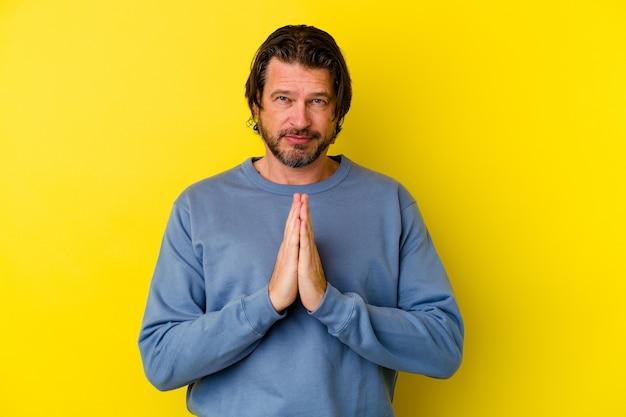 Blanke man van middelbare leeftijd geïsoleerd op gele muur bidden, toewijding, religieuze persoon op zoek naar goddelijke inspiratie.