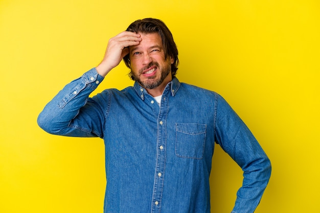 Blanke man van middelbare leeftijd geïsoleerd op gele muur iets vergeten, voorhoofd met handpalm slaan en ogen sluiten
