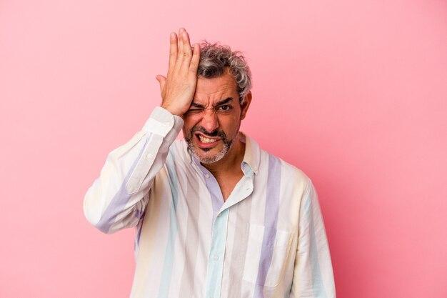 Blanke man van middelbare leeftijd geïsoleerd op roze achtergrond iets vergeten, voorhoofd slaan met palm en ogen sluiten.
