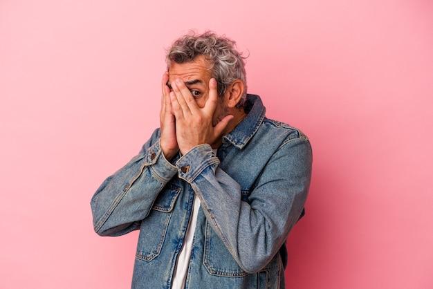 Blanke man van middelbare leeftijd geïsoleerd op roze achtergrond knipperen door vingers bang en nerveus.