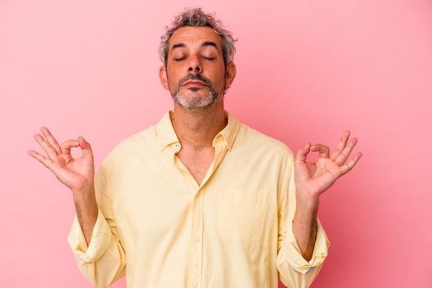 Blanke man van middelbare leeftijd geïsoleerd op roze achtergrond ontspant na een zware werkdag, ze voert yoga uit.
