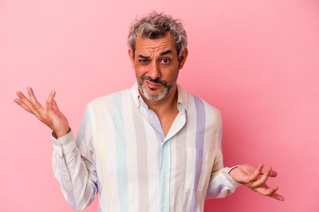 Blanke man van middelbare leeftijd geïsoleerd op roze achtergrond twijfelend en schouderophalend in vragend gebaar.