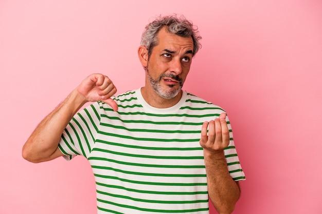 Blanke man van middelbare leeftijd geïsoleerd op roze achtergrond waaruit blijkt dat ze geen geld heeft.
