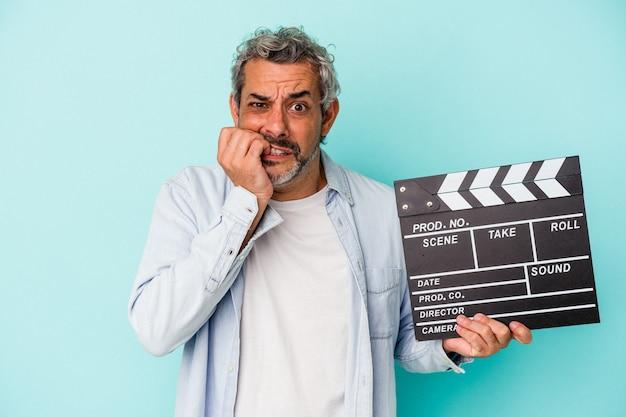 Blanke man van middelbare leeftijd met een filmklapper geïsoleerd op blauwe achtergrond bijtende nagels, nerveus en erg angstig.