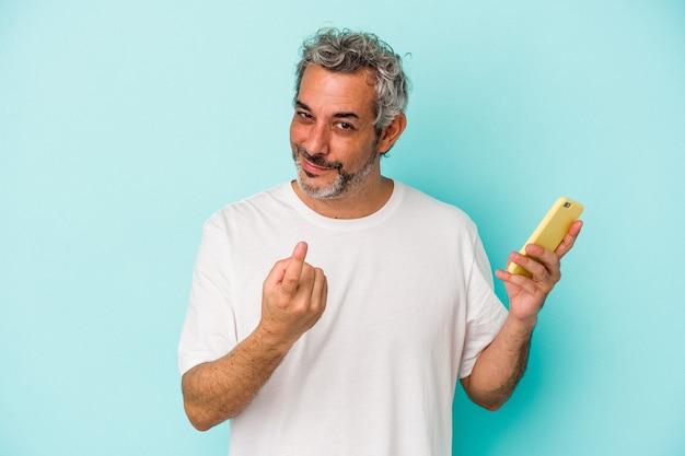 Blanke man van middelbare leeftijd met een mobiele telefoon geïsoleerd op een blauwe achtergrond die met de vinger naar je wijst alsof uitnodigend dichterbij komt.