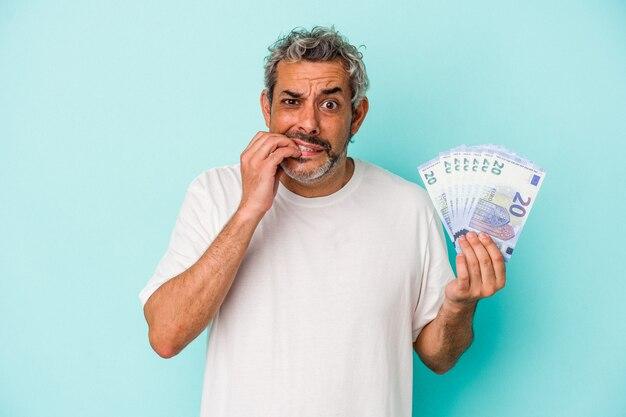 Blanke man van middelbare leeftijd met rekeningen geïsoleerd op blauwe achtergrond vingernagels bijten, nerveus en erg angstig.