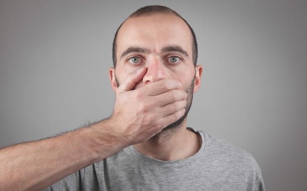 Blanke man voor zijn mond met hand geheim
