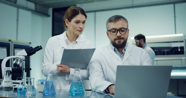 Blanke man wetenschapper in de witte robe en bril werkt op de laptopcomputer over wat onderzoek terwijl zijn vrouwelijke collega komt met enkele documenten of resultaten en iets vraagt