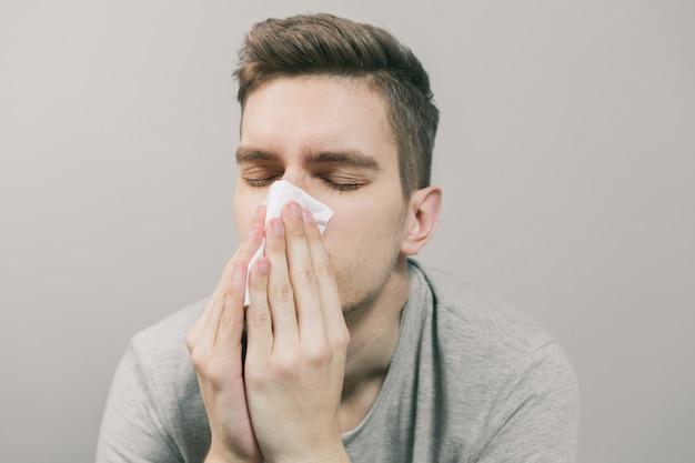 Blanke man wordt ziek en snuit zijn neus in een wit servet