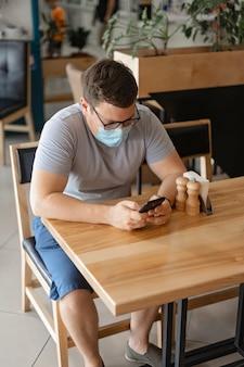 Blanke man zit in restaurant en het gebruik van telefoon in medische gezichtsmasker. nieuw normaal concept