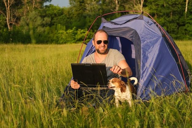 Blanke man zit in tent met chihuahua-hond, terwijl hij op laptop werkt. zelfstandig kamperen. reis met huisdieren.hoge kwaliteit foto