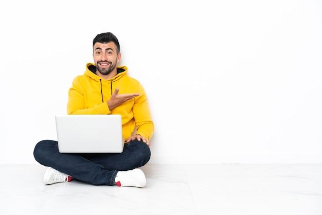 Blanke man zittend op de vloer met zijn laptop die een idee presenteert terwijl hij glimlachend naar kijkt