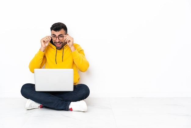 Blanke man zittend op de vloer met zijn laptop met bril en verrast