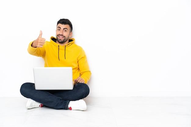 Blanke man zittend op de vloer met zijn laptop met duimen omhoog omdat er iets goeds is gebeurd