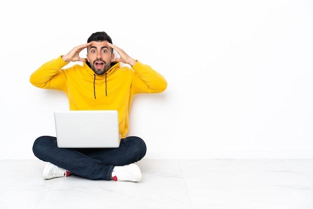 Blanke man zittend op de vloer met zijn laptop met een verbaasde uitdrukking