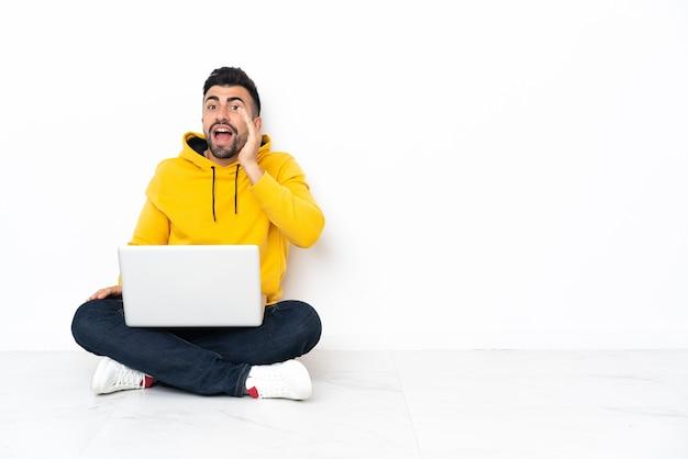Blanke man zittend op de vloer met zijn laptop schreeuwen met wijd open mond