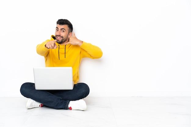 Blanke man zittend op de vloer met zijn laptop telefoongebaar maken en naar voren wijzen