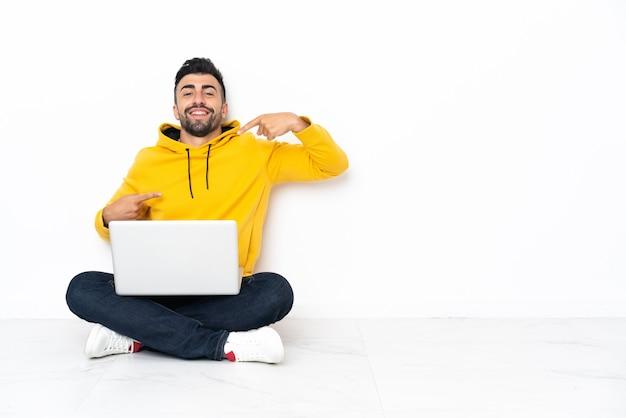 Blanke man zittend op de vloer met zijn laptop trots en zelfvoldaan