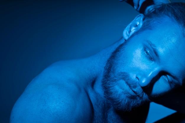 Blanke man zonder shirt in blauwe tinten