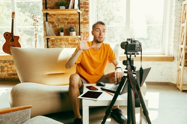 Blanke mannelijke blogger die met camera videoreview van gadgets thuis opneemt