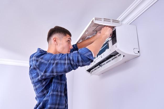 Blanke mannelijke meester in blauw shirt reinigt filters, installeert en repareert airconditioner binnenshuis