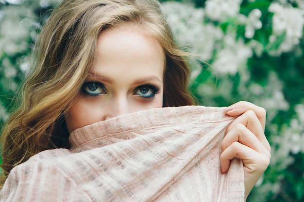 Blanke meisje bedekt haar gezicht met een zakdoek op de achtergrond van bomen.