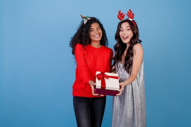 Blanke meisje en zwarte vrouw met geschenkdoos