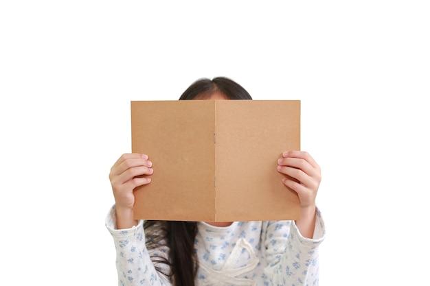 Blanke meisje kind leesboek op witte achtergrond. kind met bruine boekomslag verbergt haar gezicht - uitknippad